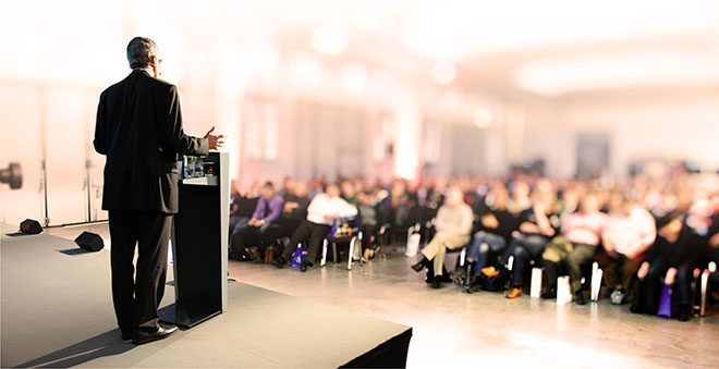 Man giving speech infront of a large audience